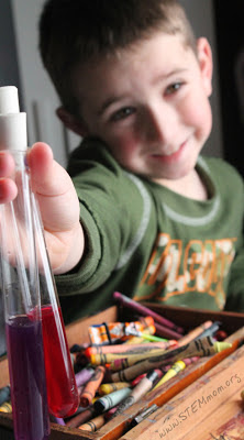 Boy smiling with colored solutions in 2 test tubes; pH lab from STEMmom.org