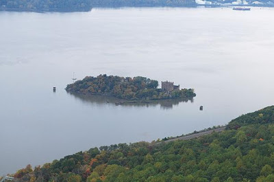 Haunted Bannerman Castle can be seen on the right of Pollepel Island in the Hudson River, New York in this view from atop a nearby mountain.  The rail road line that runs along the eastern shore of the Hudson can be seen in the foreground and offers one of the best views of the castle from the shore.