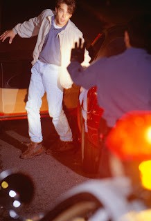 Photo of an alleged drunken driver being tested being given sobriety test by police.