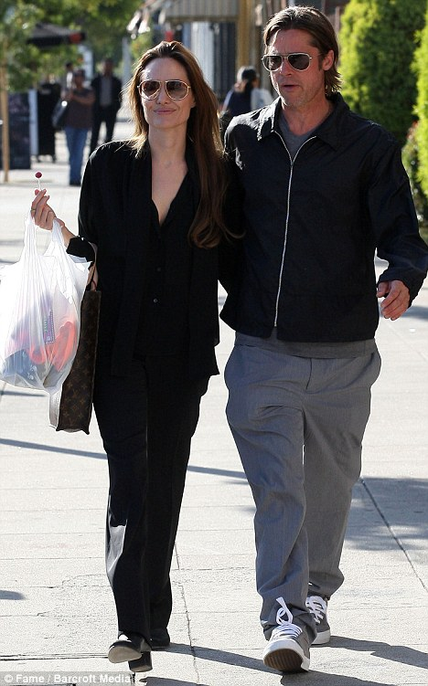Relaxed Angelina Jolie sucks on a lollipop as she goes on a romantic shopping date with Brad Pitt