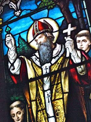 San Patricio sostiene una cruz en alto en una vidriera de colores