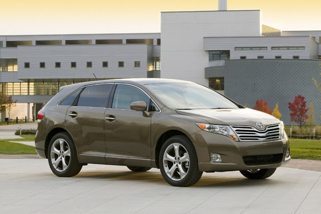 Front 3/4 view of brown 2011 Toyota Venza parked in front of building