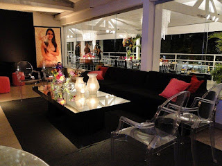 lounge moderno, mesa espelhada, poltrona Louis Ghost transparente, sofá preto, flores coloridas