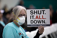 A woman holds a sign while attending a public hearing on January 16 regarding the massive natural-gas leak near Porter Ranch, California. (Photo Credit: David McNew | Stringer) Click to Enlarge.