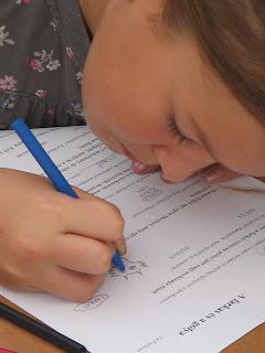 Olvasni tudó lányka a szövegértéses feladatlapra koncentrál, szinte belebújik a lapba. Épp kék zsírkrétával rajzolja meg a farkas szemét.