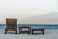 Strand mit Holzliegen und Meer im Hintergrund
