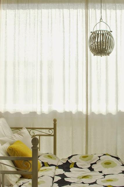 Makuuhuone parvekkeella - Askon rautasohva levitettynä, Marimekon lakanat ja Pentikin lyhty