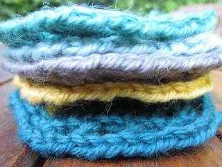 close up of stacked crochet motifs, blue grey and yellow