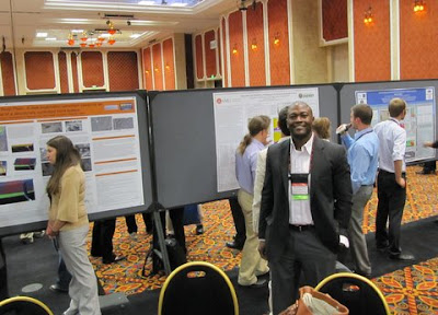 Competition manager Desmond Stubbs of DOE's Oak Ridge Institute  for Science and Education (ORISE) standing in front of the  three finalist posters