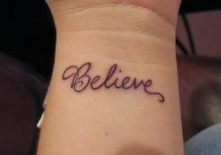 Chica con un tatuaje de frase en la muñeca que dice believe