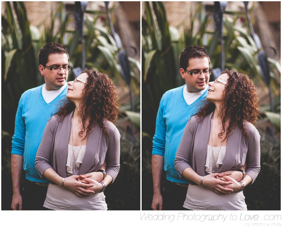 Couples looking at each other with green around for engagement photo shoot