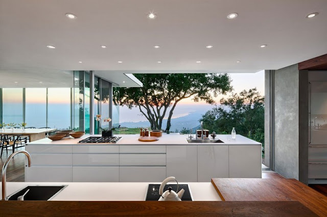 Kitchen in Home with White Counter and Long Island near Wide Glass Walls