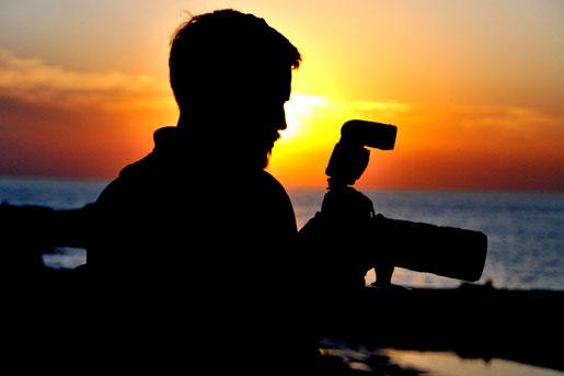 [Isaac Pacheco prepara su cámara para captar los colores del atardecer montevideano. U.S. Embassy photo: Pablo Castro]