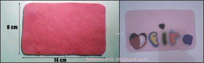Siapkan kain flanel ukuran 8 X 14 cm. Kemudian tempelkan hiasan di