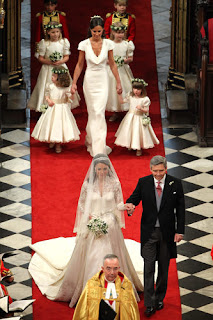 Kate Middleton makes her way down the aisle on the arm of her father Michael and followed by her sister and Maid of Honor Pippa Middleton and her bridesmaids.