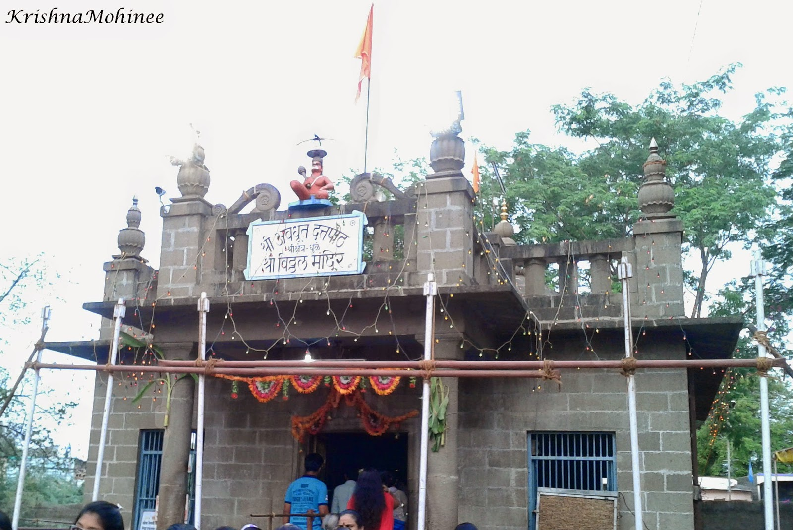 Image : Front side of Lord Vitthala Temple decorated with flowers and lights. Bhagwan Hanumanji Moorti just about the Door with Saffron Flags