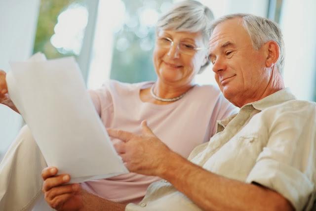пожилая пара читает на диване