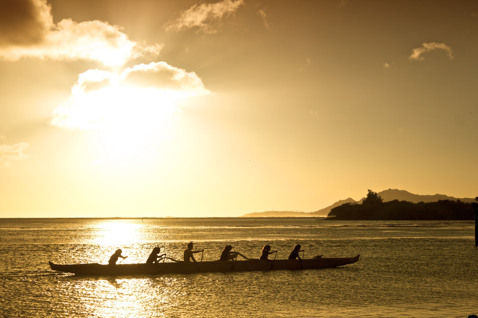 Outrigger Canoe paddlers practicing at sunset, O'ahu