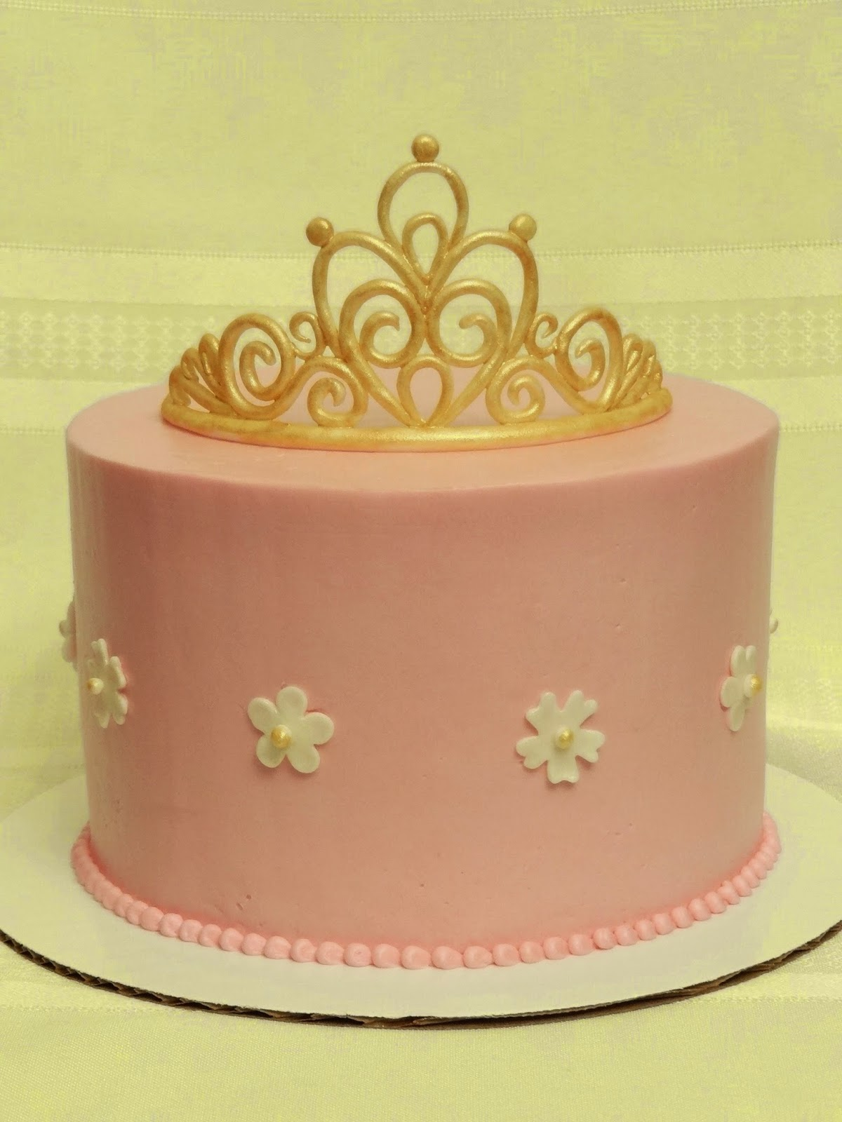 pink and gold baby shower cake with a gold fondant tiara and fondant