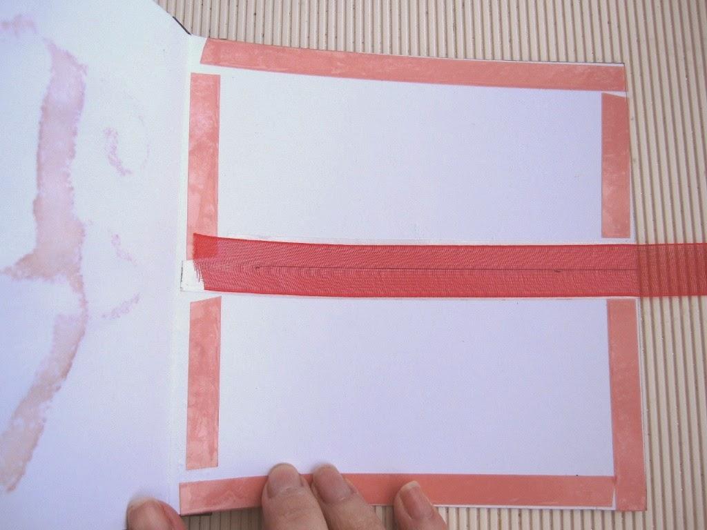 paso 6a tutorial mini-álbum scrapbook, interior de la tarjeta con cinta adhesiva de doble cara pegada en los bordes y en el centro cinta de gasa roja para uno de los cierres