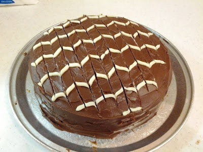 chocolate frosted cake with alternating curled white stripe details