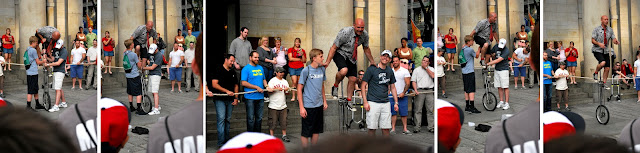 Five photos of various stages of Shane helping the street performer get on his tall unicycle.