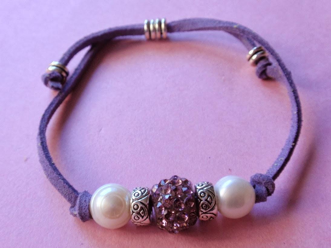 Pulsera ajustable en antelina color morado con cristal en el centro del mismo tono y perlas de agua dulce a los lados.