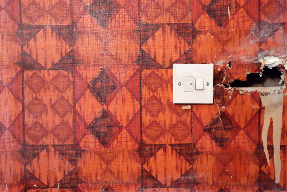 Hole in a wall covered in orange 60s geometric wallpaper. Not all bloggers live in pristine white palaces.