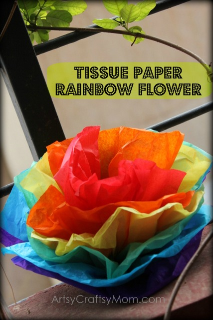 Rainbow flower made of rainbow tissue paper that is red, orange, yellow, green, blue, and purple.