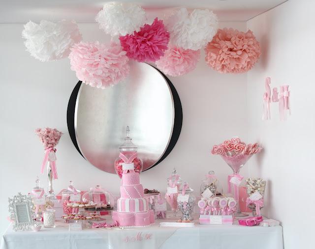 Mesa de dulces con pompones de papel rosa