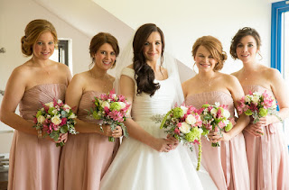 Bride poses with her bridesmaids holding their flower bouquets