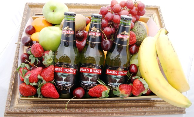 fruit and beer hamper flowing out of gold frame