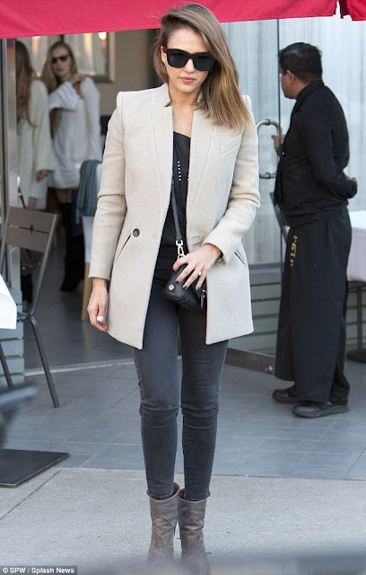 Jessica Alba in a casual outfit of black jeans, black sweater, cream coat, and taupe boots