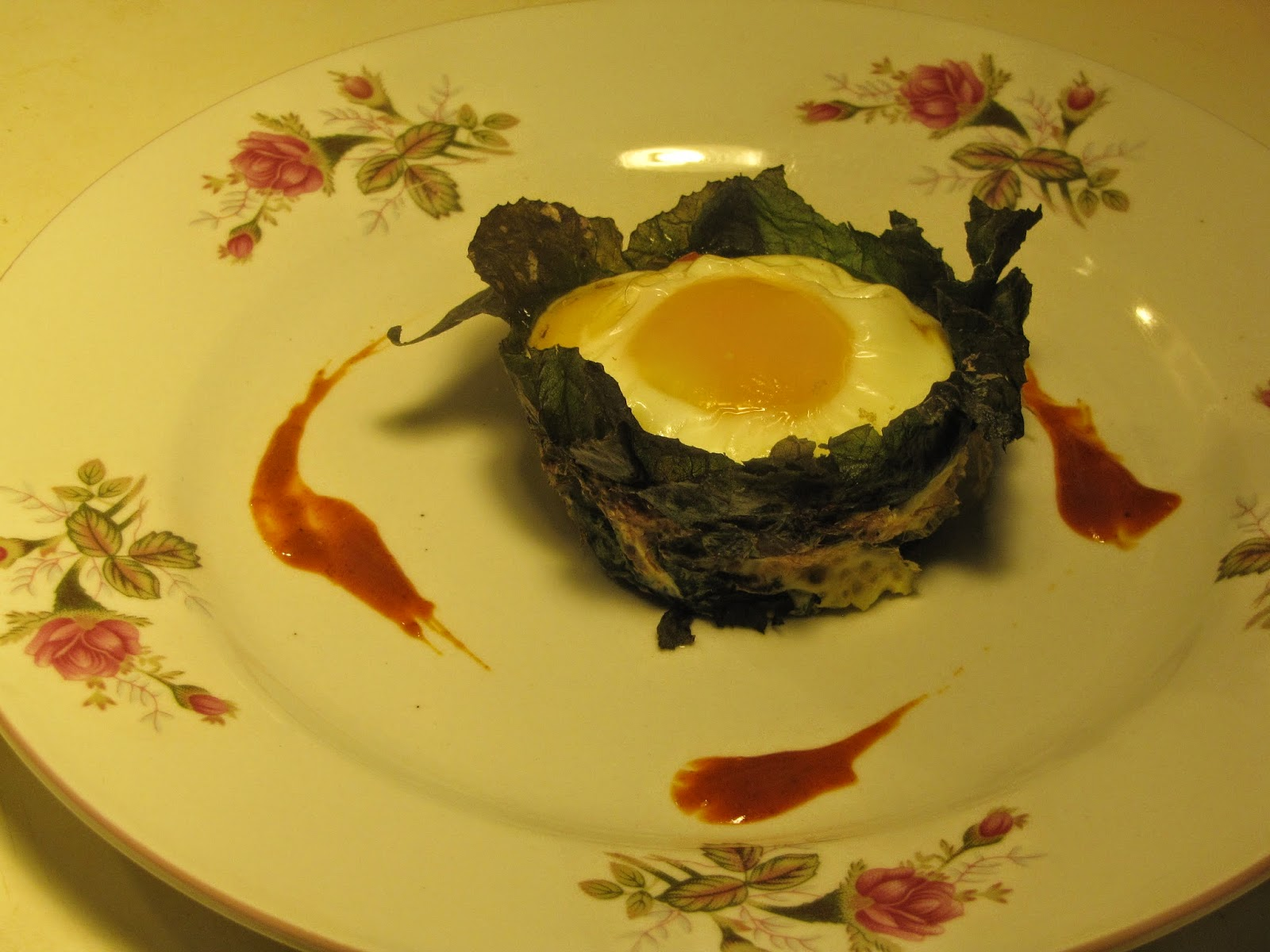 Baked egg in a collard green cup presented on plate with drippings of hot sauce