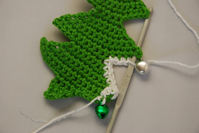 Crochet Christmas tree pattern and tutorial: image of positioning the bauble before crocheting the next stitch
