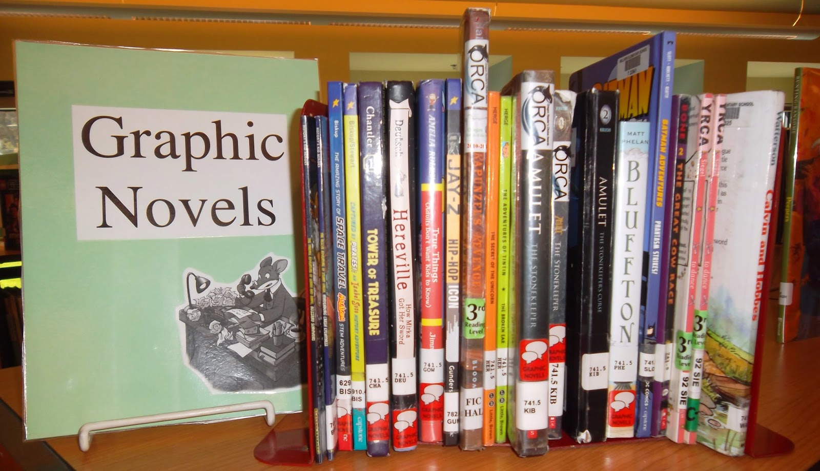 "Graphic novels shelved between bookends. At left, a sign proclaiming ""Graphic Novels"" features a cut-out of cartoon rodent Geronimo Stilton at his desk"