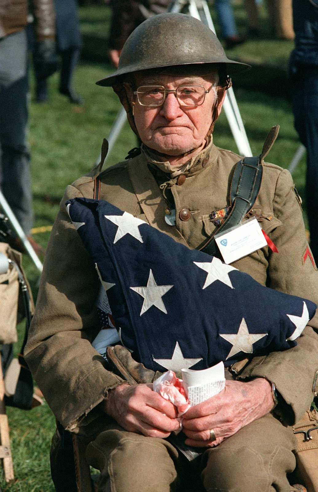 40 Amazing Historical Pictures - Joseph Ambrose, an 86-year-old World War I veteran, watches the dedication day parade for the Vietnam Veterans Memorial. He is holding the flag that covered the casket of his son, who was killed in the Korean War, 11/13/1982