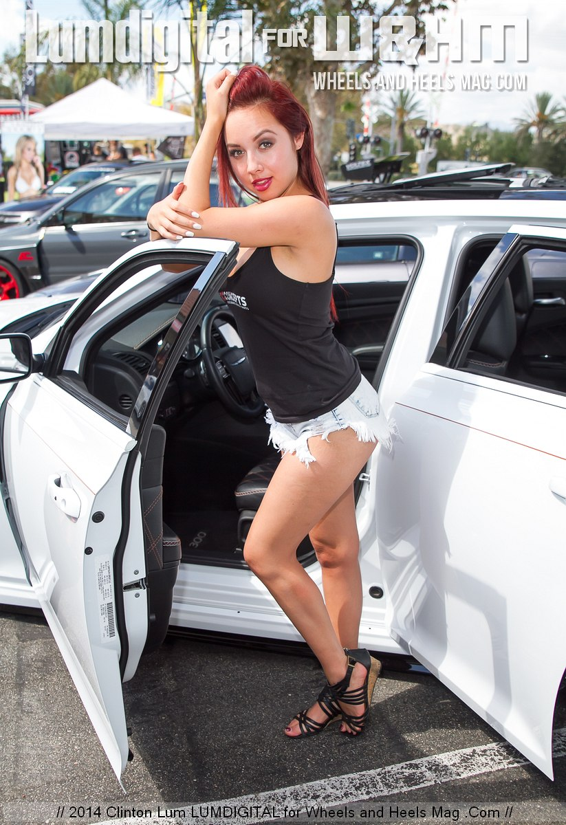 Brittani Paige by the car for R1 Concepts at the hmsphrs vaping store one year anniversary car meet