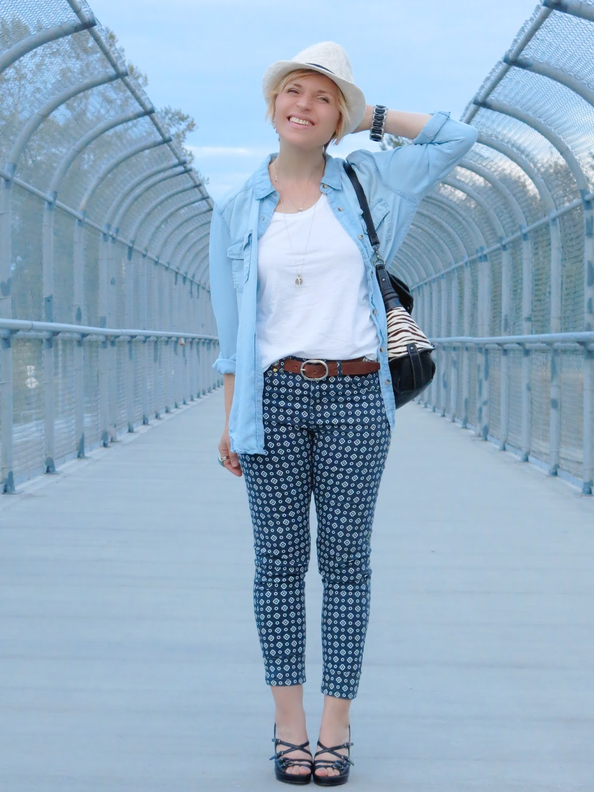 styling printed pants with a chambray shirt, strappy platform shoes, and a summer fedora