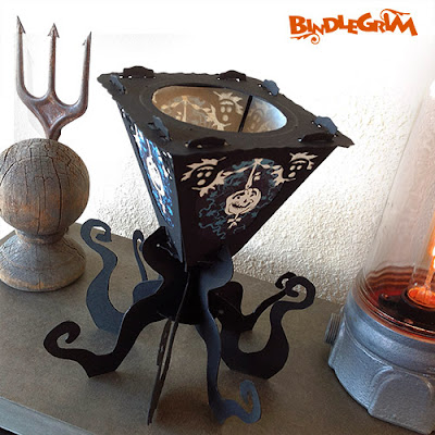 Antiques surround a vintage-style tealight lantern with eight legs and a silhouette black frame by artist Bindlegrim for the 2014 holiday season