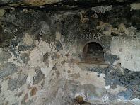 Forn de pa amb el cendrer tapiat a la dreta a la Bauma de les Set Portes