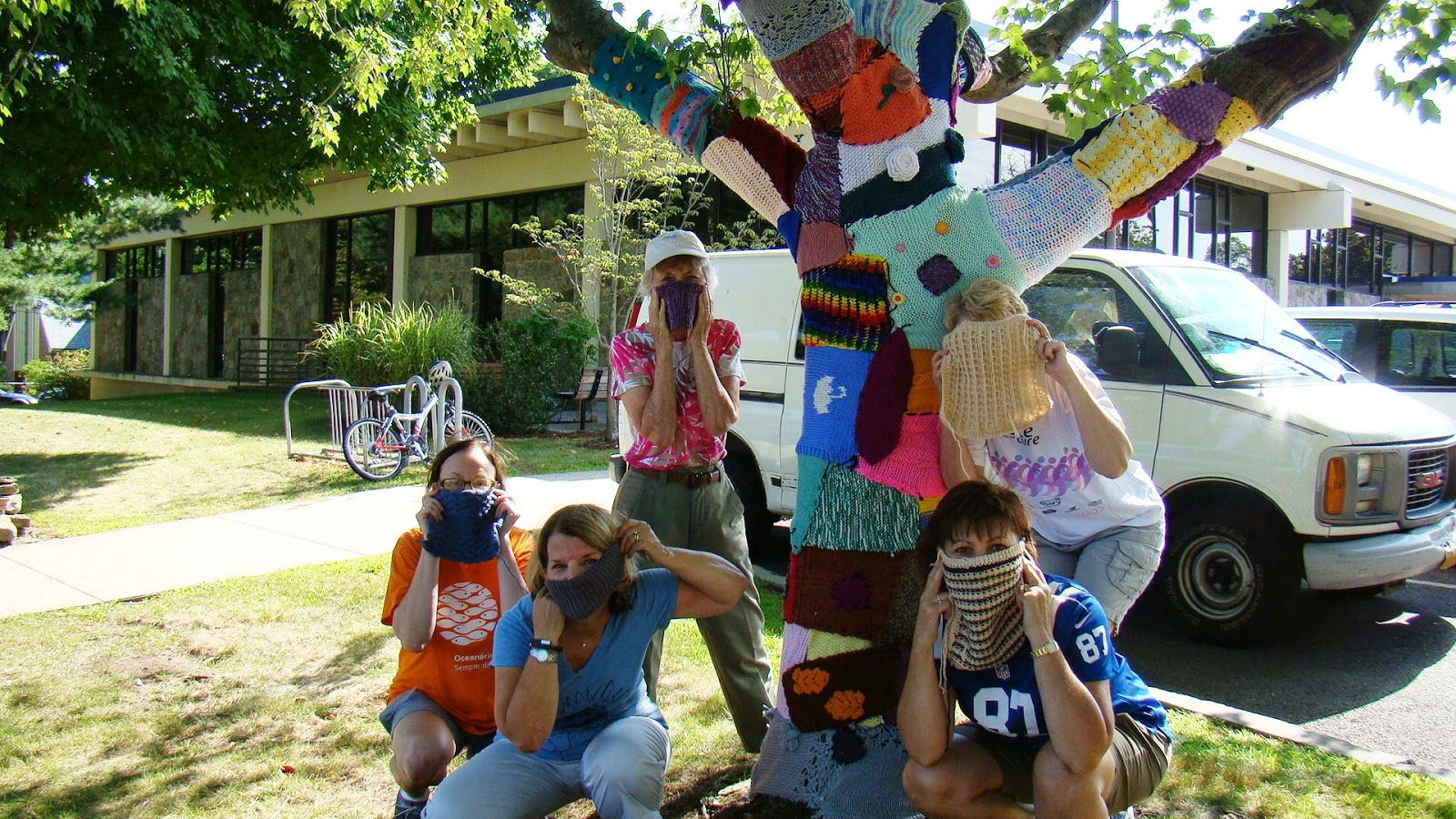 A group of women group around a tree that has been yarnbombed, covered with pieces of knitting. The women's faces are partially concealed by the colorful knitted swatches that they hold over their noses and mouths.