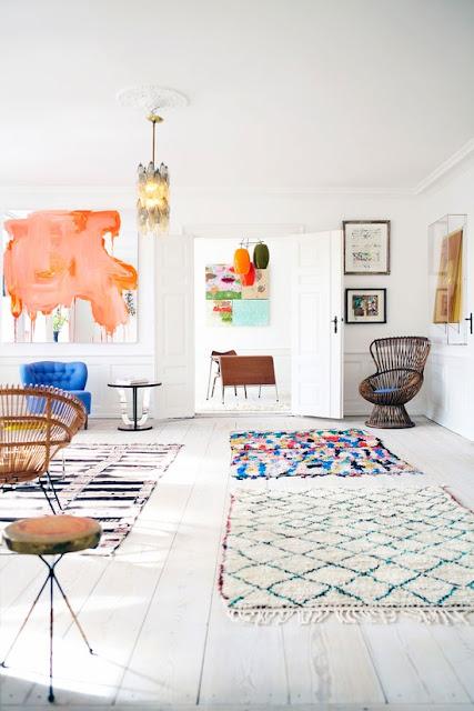 salon nordico blanco con muebles vintage de mimbre y alfombras de lana