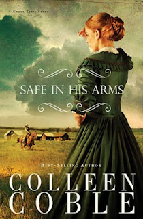 cover of Safe in His Arms by Colleen Coble shows a woman wearing a dark green dress shading her eyes looking out over the prairie toward a man on horseback and some log cabins