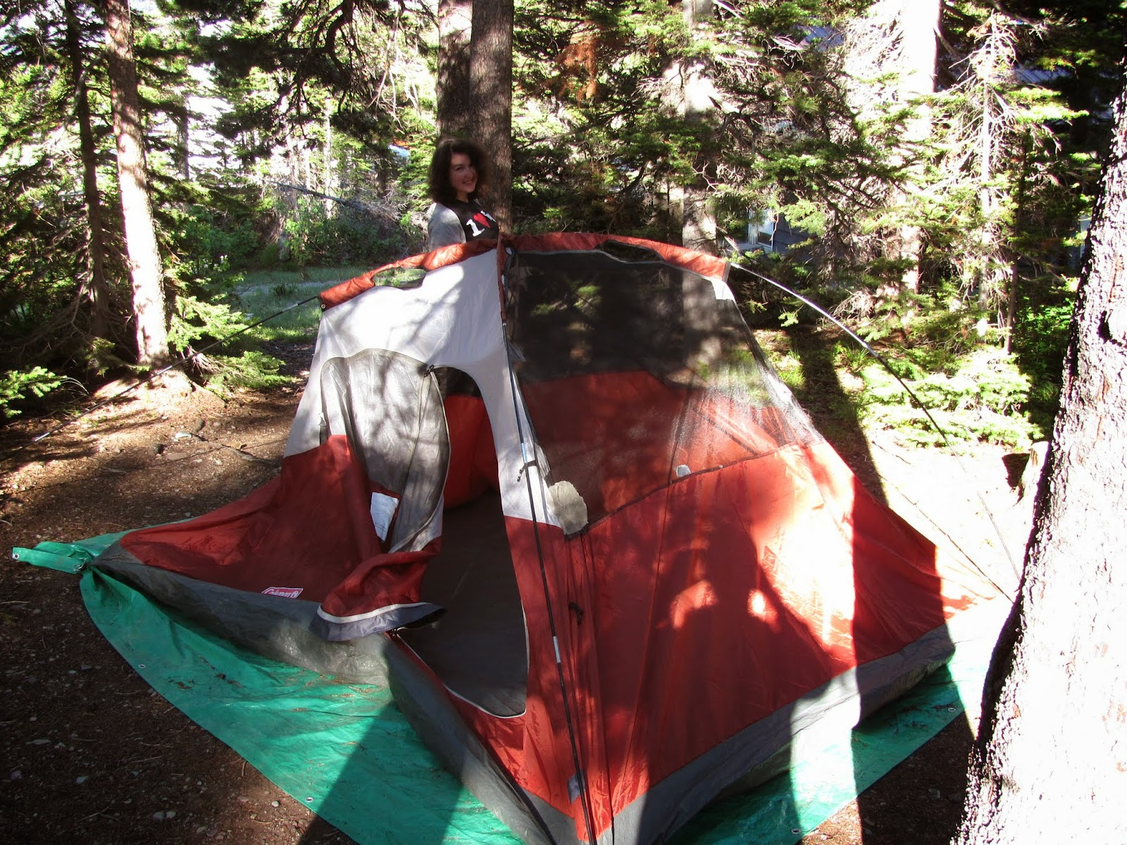 Sara is rolling up our orange Coleman tent at Two Medicine in Glacier National Park in Montana