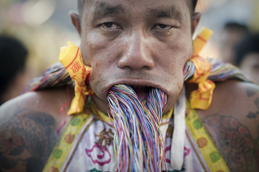 70 Of The Most Touching Photos Taken In 2015 - A devotee of the Chinese Bang Neow shrine pierces his cheeks with electrical wire to celebrate the annual vegetarian festival in Phuket, Thailand. The painful acts are said to purify participants.