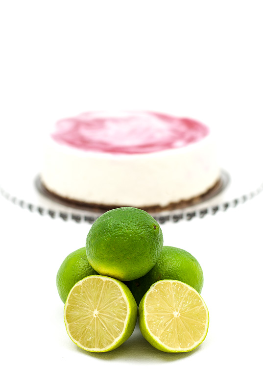Raw lime-coconut-raspberry marmorin cake focus on limes