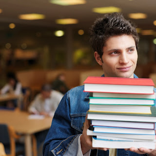 Young male college student carrying an armful of books.