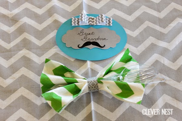 chevron bow tie napkins with washi tape and family name tags. More ideas for a Little Man baby shower at Clever Nest #aquagraylime #boysfirstbirthday #hipsterparty #littlemantheme #clevernest #babyshowergameideas