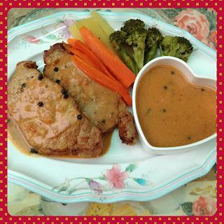ภาพใหญ่ของสเต็กหมู โรยด้วยพริกไทยดำ เคียงด้วยซอส และผักต้ม (แครอท มันฝรั่ง และบรอกโคลี)